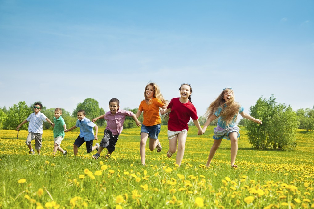 children running and laughing in field